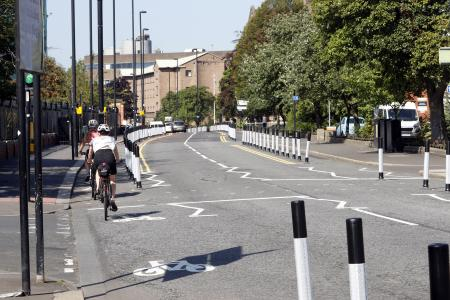 Photo showing a main road with people using a temporary cycle lane heading away from the camera.