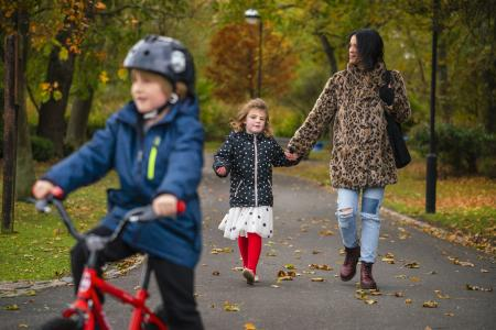 image of cghild cycling in park with mother and sister walking in the background