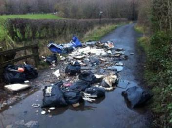 fly tip in road and puddle
