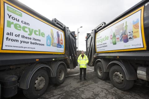 Cllr Nick Kemp photographed with the current fleet of recycling wagons.