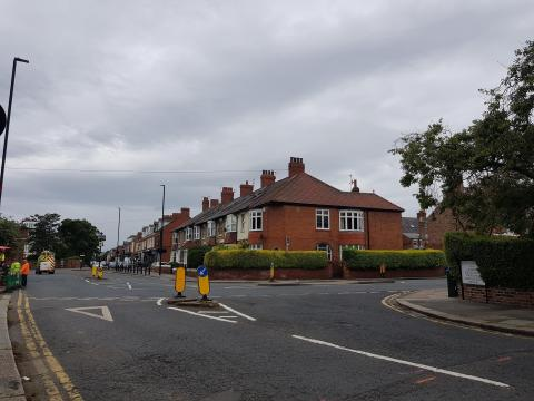 Photo showing a  junction between two roads with houses at the side of the road.