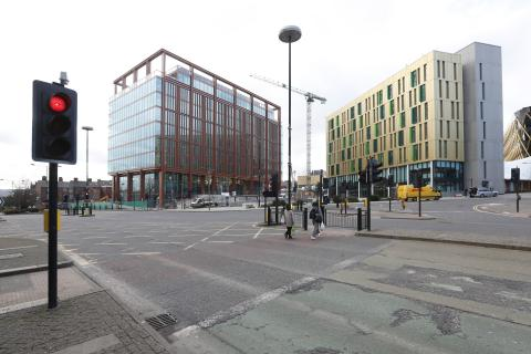 Photo showing a road junction with traffic lights, two people crossing and two large buildings in the background.