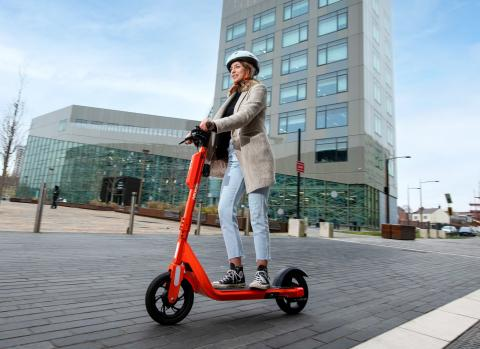 Photo showing a young woman using an orange e-scooter on a clear road with a tall building in the background. She is wearing light coloured clothing and a white helmet.