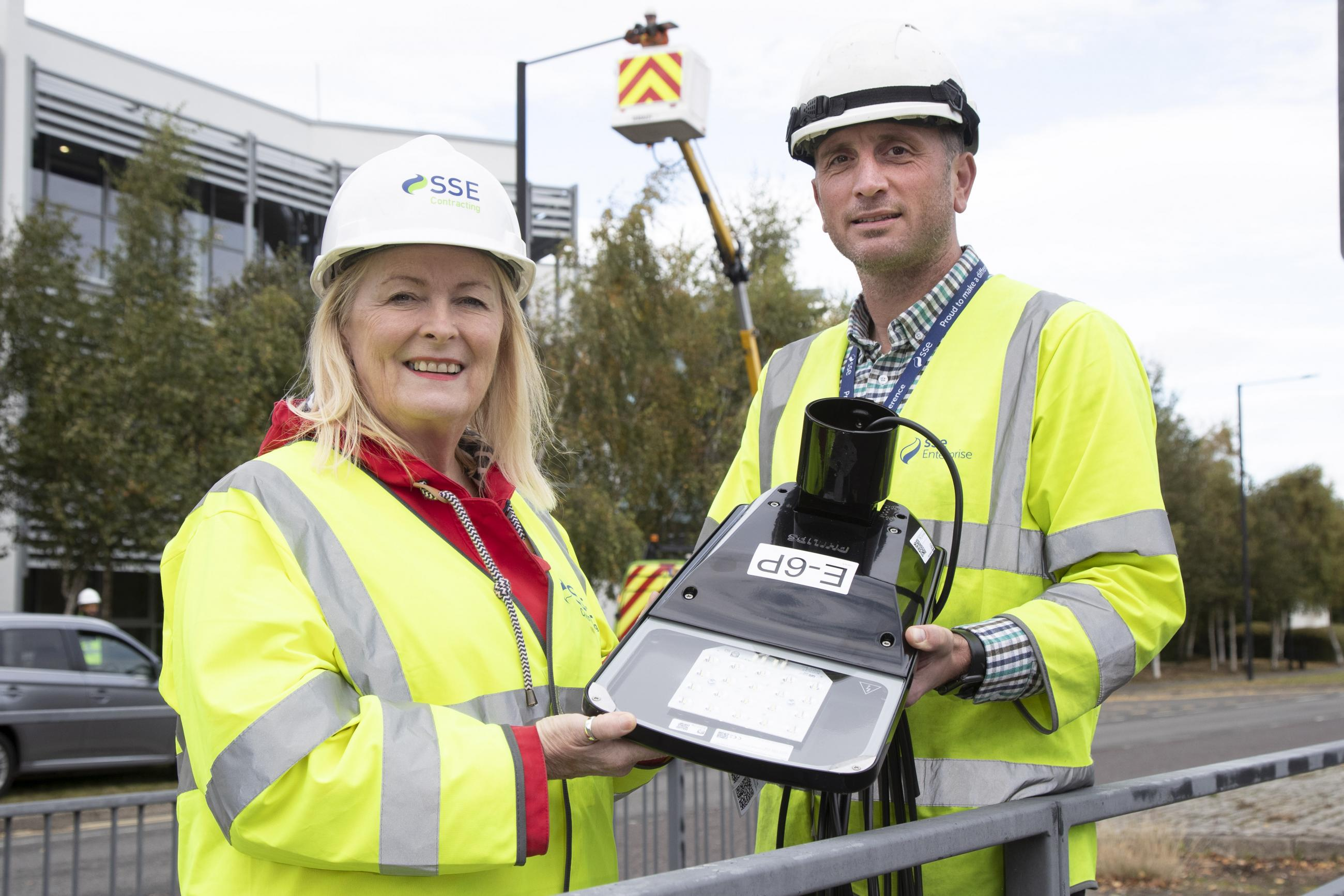 Photograph showing two people in hard hats and high vis jackets holding the lamp for a new street light.